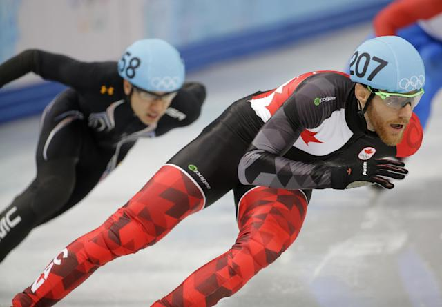 Olivier Jean of Canada, right, and J.R. Celski of the United States compete in a men's 500m short track speedskating heat at the Iceberg Skating Palace during the 2014 Winter Olympics, Tuesday, Feb. 18, 2014, in Sochi, Russia. (AP Photo/David J. Phillip )