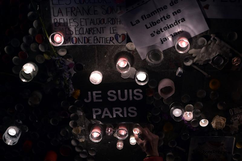 A woman lights a candle next to a letter reading 'I am Paris' in French, as thousands of people gather at the central square in Strasbourg, eastern France, on November 18, 2015, to pay tribute to the victims of the attacks of November 13 (AFP Photo/Patrick Hertzog)
