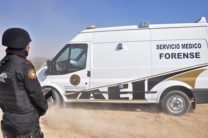 A Nuevo Leon state police officer stands guard on a dirt road leading to a ranch as a forensic a vehicle leaves near the town of Mina, in northern Mexico, Monday, Jan. 28, 2013. At least eight bodies were found in a well near this ranch on Sunday near the site where 20 people went missing late last week, including members of a Colombian-style band, according to a state forensic official. Officials could not confirm whether the bodies belonged to 16 members of the band Kombo Kolombia and their crew, who were reported missing late last week after playing a private show in a bar in the neighboring town of Hidalgo north of Monterrey. (AP Photo/Emilio Vazquez)