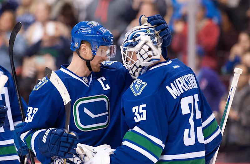 Henrik Sedin (L) of the Vancouver Canucks congratulates goalie Jacob Markstrom on April 13, 2014 at Rogers Arena in Vancouver