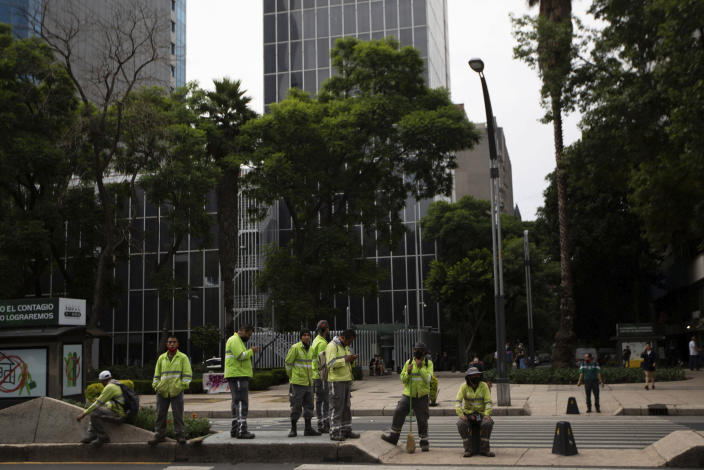 Ground workers stand in the median of Reforma Avenue after a 7.5 earthquake, in Mexico City, Tuesday, June 23, 2020. The earthquake centered near the resort of Huatulco in southern Mexico swayed buildings Tuesday in Mexico City and sent thousands into the streets. (AP Photo/Fernando Llano)