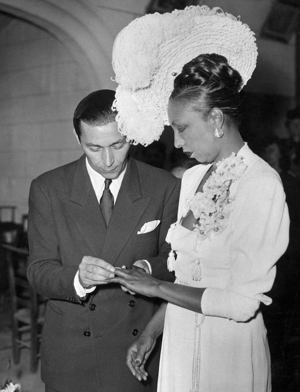 """<p>For her fourth marriage to French actor Jo Buillon, Josephine Baker stunned in a square neck sheath dress and white feathered hat. They said """"I do"""" in the chapel on the grounds of her chateau, Les Milandes, in 1947. The couple went on to adopt 12 children together and were married until 1961. </p>"""