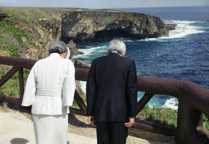 FILE - In this June 28, 2005, file photo, Emperor Akihito, right, accompanied by Empress Michiko bow to the infamous Banzai Cliff, or Puntan Sabaneta, in Saipan, to offer prayers for the Japanese soldiers and civilians who jumped off the rocky cliff 60 years ago to avoid being captured by the U.S forces in the bloody World War Two Battle of Saipan. Akihito has visited World War II battle sites, including Okinawa and the Pacific island of Saipan, and prayed for the dead on both sides, repeatedly expressing remorse for Japan's past military aggression. (Eriko Sugita/U.S. Pool Photo via AP, File)