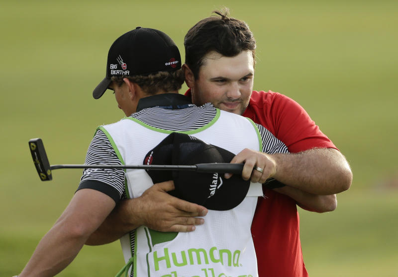 Patrick Reed, right, hugs his caddie Kessler Karain after winning the Humana Challenge golf tournament on the Palmer Private course at PGA West Sunday, Jan. 19, 2014 in La Quinta, Calif. (AP Photo/Chris Carlson)