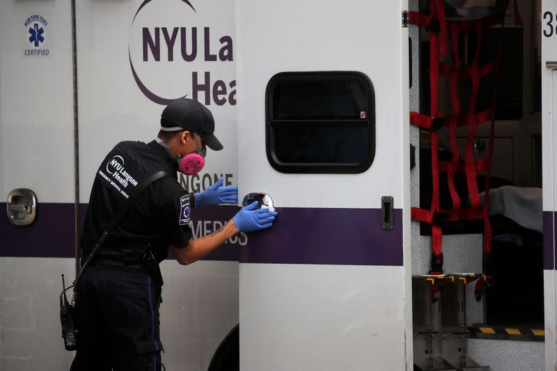 Paramedic cleans ambulance outside Maimonides Medical Center during outbreak of coronavirus disease (COVID-19) in Brooklyn New York