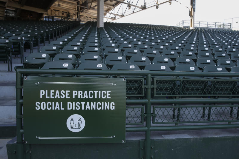 A sign inside Wrigley Field requires guest to practice social distancing amid the coronavirus pandemic during Chicago Cubs baseball training camp on Sunday, July 5, 2020 in Chicago. (AP Photo/Kamil Krzaczynski)