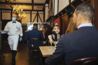 Wax statues of Audrey Hepburn and Michael Strahan occupy one of the tables at Peter Luger Steakhouse on Friday, Feb, 26, 2021, in New York. Five statues, on loan from Madame Tussauds, will occupy unused tables during COVID-19 occupancy restrictions. (AP Photo/Kevin Hagen)