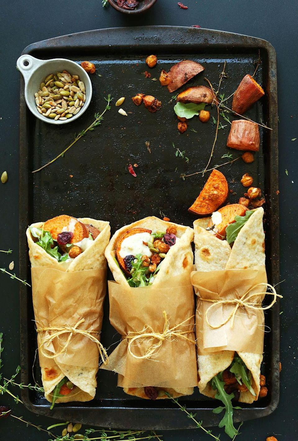 """<p>Everyone at the dinner table will be reaching for one of these wraps. They're filled with cinnamon-roasted <a href=""""https://www.countryliving.com/food-drinks/g877/sweet-potato-recipes-1009/"""" rel=""""nofollow noopener"""" target=""""_blank"""" data-ylk=""""slk:sweet potatoes"""" class=""""link rapid-noclick-resp"""">sweet potatoes</a>, crispy baked chickpeas, and toasted pumpkin seeds all rolled in a garlic herb flatbread. </p><p><strong>Get the recipe at <a href=""""https://minimalistbaker.com/vegan-thanksgiving-wraps/"""" rel=""""nofollow noopener"""" target=""""_blank"""" data-ylk=""""slk:Minimalist Baker"""" class=""""link rapid-noclick-resp"""">Minimalist Baker</a>.</strong> </p>"""