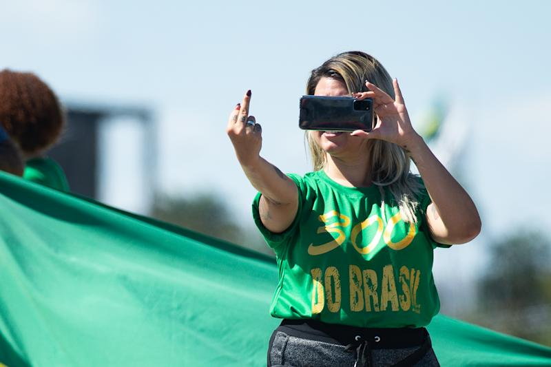 "BRASILIA, BRAZIL - JUNE 13: Sara Winter, the leader of the extreme right group ""300 do Brasil"" and supporter of Brazilian President Jair Bolsonaro, films with her cell phone during protest against the President amidst the coronavirus (COVID-19) pandemic at the Esplanada dos Ministérios on June 13, 2020 in Brasilia. Sara Winter was arrested on June 15 by the Federal Police as part of an investigation into the financing of anti-democratic protests. (Photo by Andressa Anholete/Getty Images)"