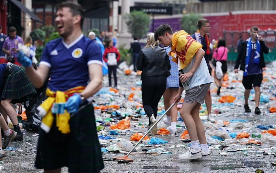 Scotland fans clean up litter in Leicester Square, London, ahead of the UEFA Euro 2020 Group D match between England and Scotland - PA
