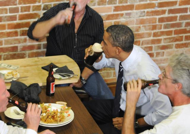 U.S. President Barack Obama (2nd R) drinks a glass of Guinness as he shares a toast during a meeting with unemployed construction workers at the Harp and Celt pub in Orlando, Florida October 11, 2011. REUTERS/Jonathan Ernst (UNITED STATES - Tags: BUSINESS CONSTRUCTION POLITICS FOOD SOCIETY EMPLOYMENT)