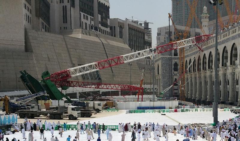 Pilgrims walk past the crane that collapsed on September 11, 2015 at the Grand Mosque in Mecca