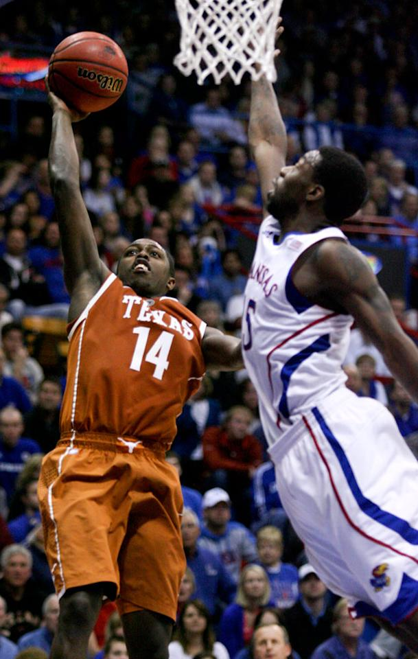 Texas' J'Covan Brown (14) shots over Kansas' Elijah Johnson (15) in the second half of an NCAA college basketball game Saturday, March 3, 2012, in Lawrence, Kan. Brown scored 33 points in a  73-63 loss to Kansas.