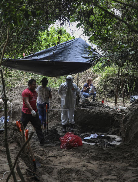 Investigators look at human remains placed in an evidence bag, dug from a clandestine grave site in Arbolillo, Veracruz state, Mexico, Friday, Sept. 7, 2018. One day after authorities in the Mexican state of Veracruz announced the discovery of at least 166 skulls in mass graves, journalists who arrived at the site Friday discovered it was the same location where authorities said they had found 47 bodies the previous year. (AP Photo/Felix Marquez)