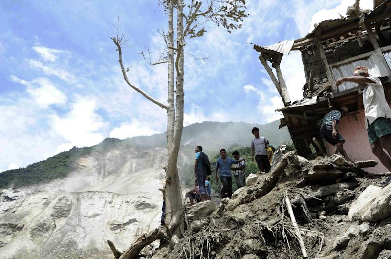In this photo released by the Nepalese Army on August 2, 2014, residents stand near damaged houses after flooding near the scene of a landslide near the Sunkoshi River northeast of Kathmandu