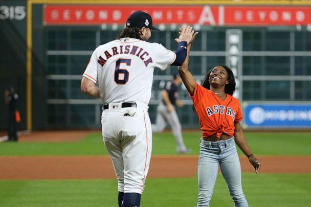 Olympic gymnastics gold medalist Simone Biles high fives Jake Marisnick after throwing out a ceremonial first pitch to Marisnick prior to game two of the 2019 World Series between the Astros and the Washington Nationals at Minute Maid Park, Oct. 23, 2019. (Troy Taormina/USA TODAY Sports via Reuters)