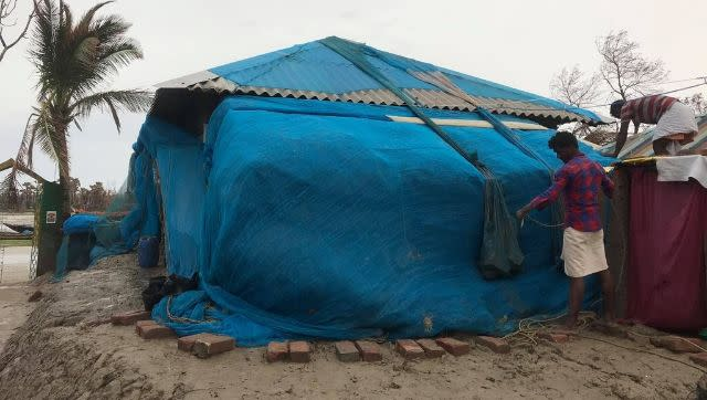 Two men pin a tarpaulin sheet to cover their home