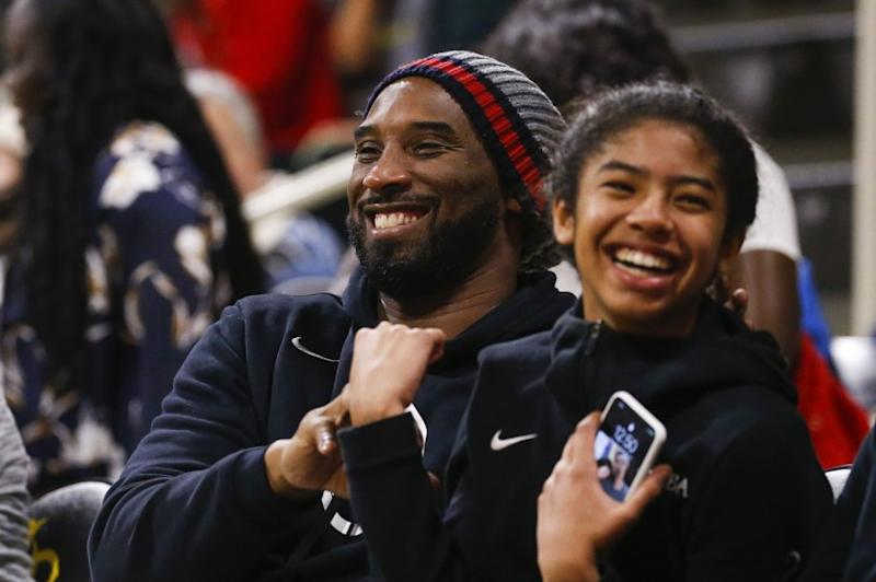 Kobe Bryant shares a laugh with his daughter, Gianna, while attending a women's basketball game between Long Beach State and Oregon on Dec. 14, 2019.