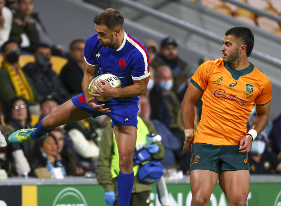 France's Melvyn Jaminet, left, catches the ball as Australia's Tom Wright watches during the rugby international between France and Australia at Suncorp Stadium in Brisbane, Australia, Wednesday, July 7, 2021. (AP Photo/Tertius Pickard)