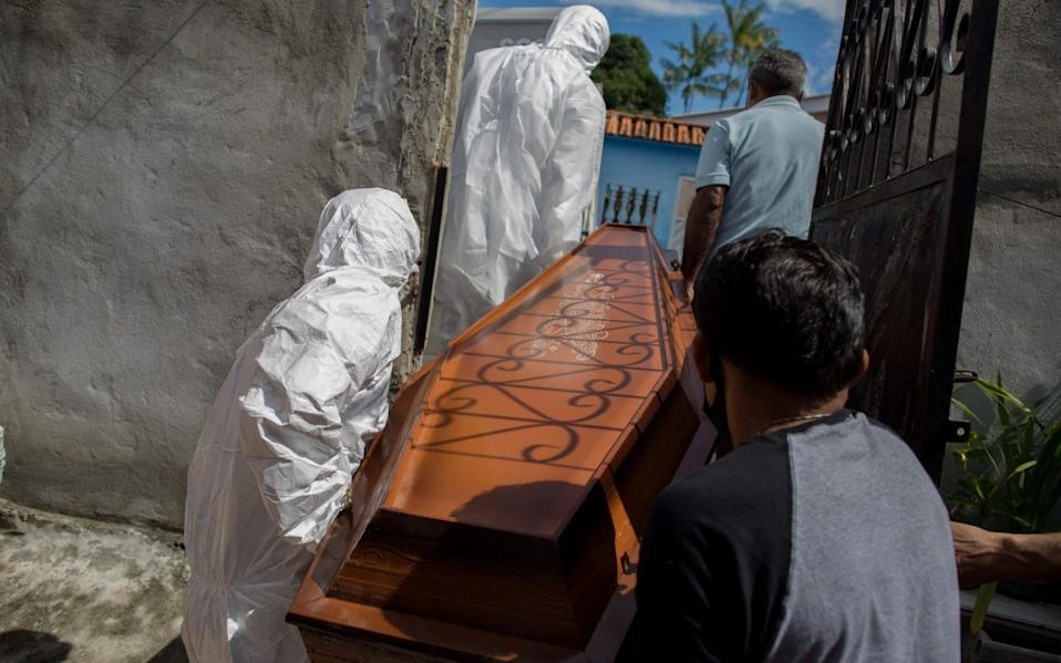 Burial workers remove the body of a man who died from Covid in Manaus, Brazil which has been hit hard by a second wave of Covid - Michael Dantas/AFP