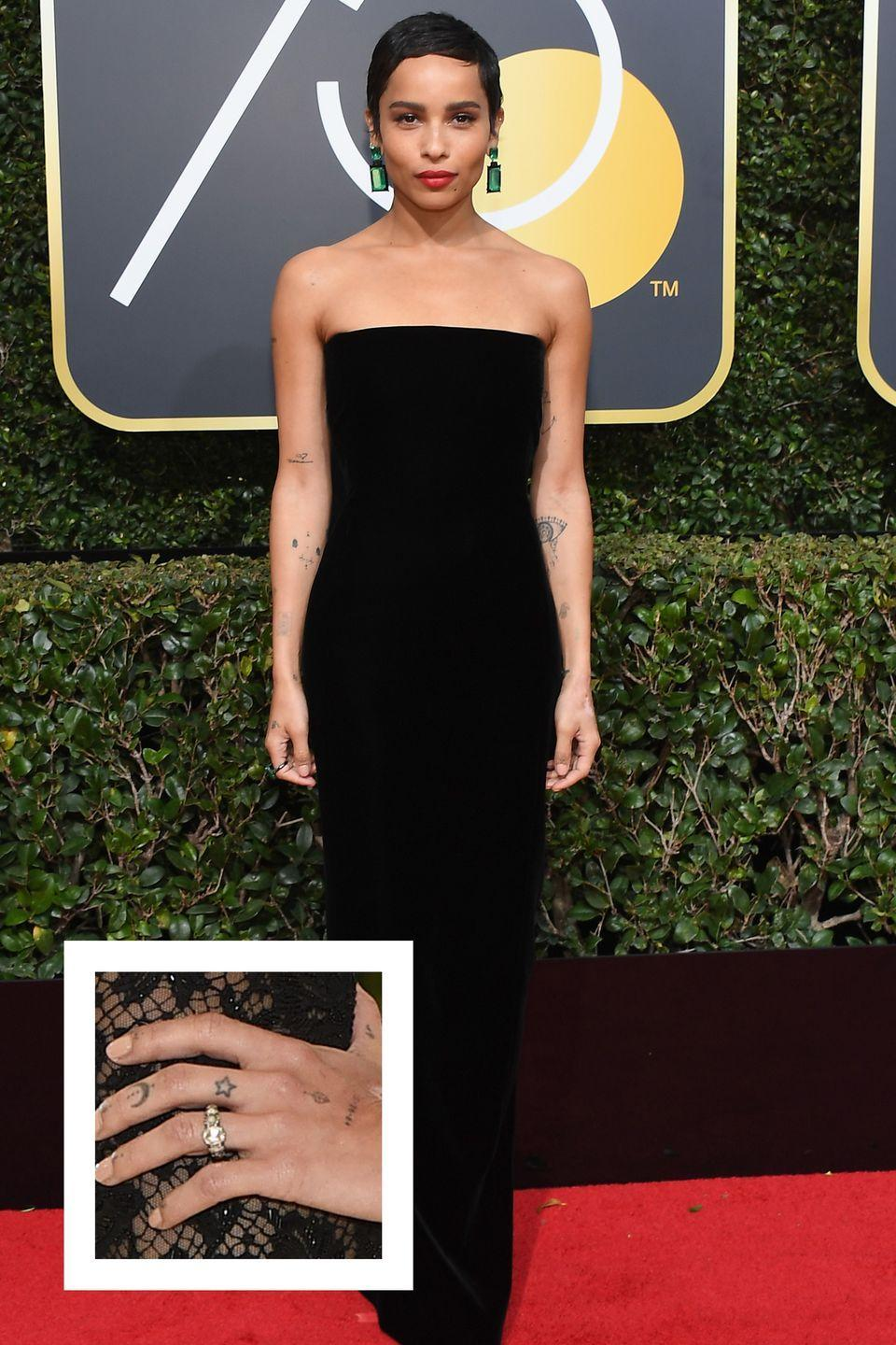 """<p>Zoë Kravitz confirmed her engagement to actor Karl Glusman <a href=""""https://www.rollingstone.com/movies/movie-features/zoe-kravitz-naked-cover-story-746684/"""" rel=""""nofollow noopener"""" target=""""_blank"""" data-ylk=""""slk:in an interview with"""" class=""""link rapid-noclick-resp"""">in an interview with</a> <em>Rolling Stone</em> in October 2018 after the pair officially got engaged in Paris in February 2018. The ring appears to be a round center stone surrounded by smaller accent stones. Kravitz told <em>Rolling Stone</em> that the ring was exactly what she had in mind. """"He nailed it,"""" <a href=""""https://www.rollingstone.com/movies/movie-features/zoe-kravitz-naked-cover-story-746684/"""" rel=""""nofollow noopener"""" target=""""_blank"""" data-ylk=""""slk:she said."""" class=""""link rapid-noclick-resp"""">she said.</a></p>"""