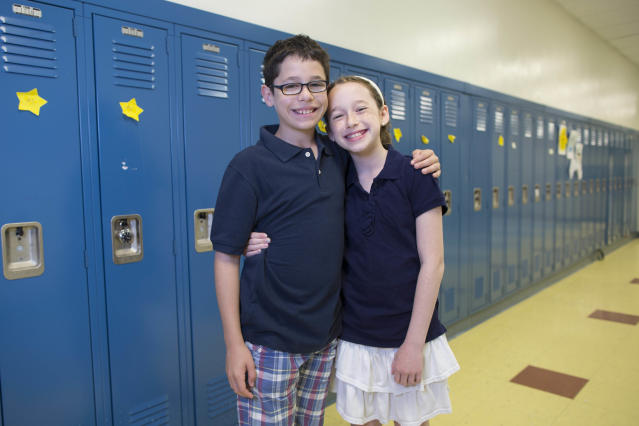 In thias Thursday, June 6, 2013 photo, Zach Becker, left, and his twin sister, Mira, one of the twenty-four sets of twins from Highcrest Middle School in Wilmette, Ill. pose for a portrait at the school. The group is attempting to break a Guinness World record for the amount of twins in one grade which is currently sixteen sets. (AP Photo/Scott Eisen)
