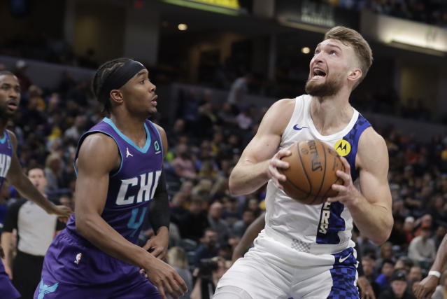 Indiana Pacers' Domantas Sabonis, right, goes to the basket against Charlotte Hornets' Devonte' Graham (4) during the second half of an NBA basketball game, Sunday, Dec. 15, 2019, in Indianapolis. (AP Photo/Darron Cummings)
