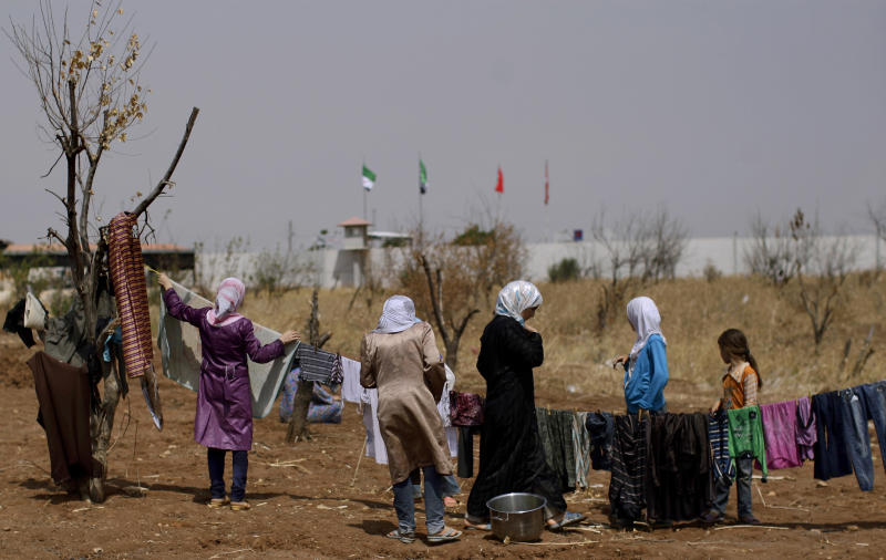 Syrian women, who fled their homes in Aleppo, due to fighting between the Syrian army and the rebels, hang their laundry in a field facing the Turkish border, as they take refuge at the Bab Al-Salameh border crossing, in hopes of entering one of the refugee camps in Turkey, near the Syrian town of Azaz, Thursday, Aug. 30, 2012. (AP Photo/Muhammed Muheisen)