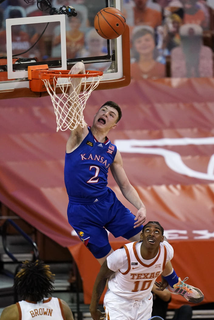 Kansas guard Christian Braun (2) drives to the basket over Texas guard Donovan Williams (10) during the first half of an NCAA college basketball game, Tuesday, Feb. 23, 2021, in Austin, Texas. (AP Photo/Eric Gay)