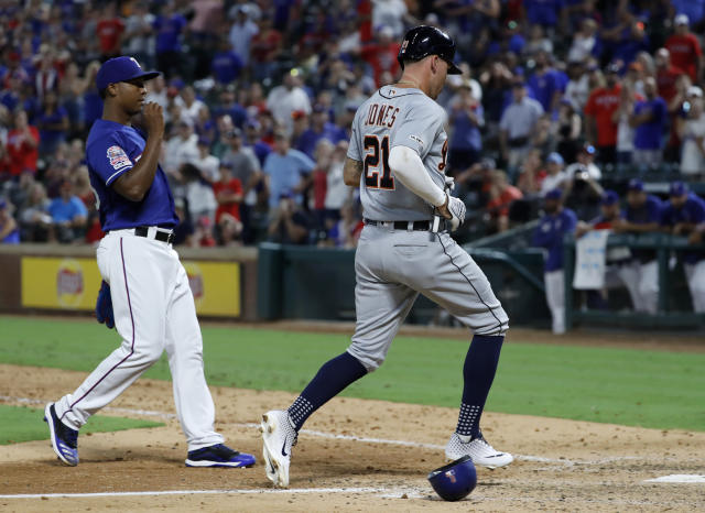 Detroit Tigers' JaCoby Jones (21) scores on a wild pitch thrown by Texas Rangers' Jose Leclerc, left, during the ninth inning of a baseball game in Arlington, Texas, Friday, Aug. 2, 2019. (AP Photo/Tony Gutierrez)