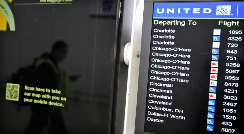FILE PHOTO: A customer is reflected in a screen showing the schedule times of United at Newark International airport in New Jersey
