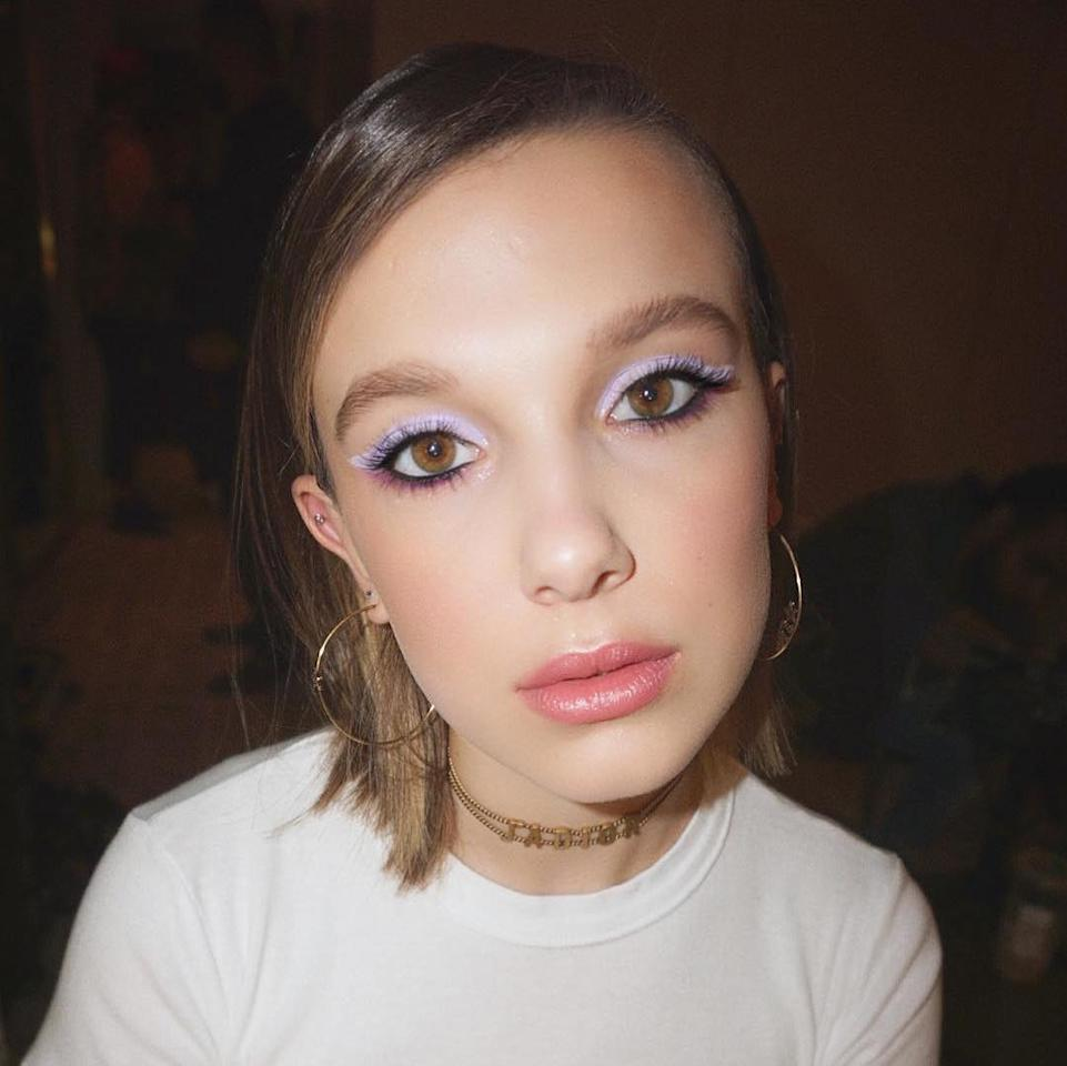 """Makeup artist Kelsey Deenihan <a href=""""https://www.instagram.com/p/BxFm7kPnWzp/"""">wrote on Instagram</a> that she sought to brighten up a gloomy day, and she totally succeeded with these varying shades of purple on Millie Bobby Brown's eyes. That incredible pastel wing? It was created with ColourPop's <a href=""""https://colourpop.com/products/cry-baby-liner"""" rel=""""nofollow"""">Cry Baby Creme Gel Liner</a>, which Deenihan used to cover the entire lid with an eye shadow brush. A berry Viseart shadow along the lower lash line, Urban Decay's classic black <a href=""""https://shop-links.co/1671917443644150218"""" rel=""""nofollow"""">Perversion pencil</a> on the waterlines, and Pat McGrath's <a href=""""https://shop-links.co/1671917503565192036"""" rel=""""nofollow"""">FetishEyes Mascara</a> complete the colorful eye look."""
