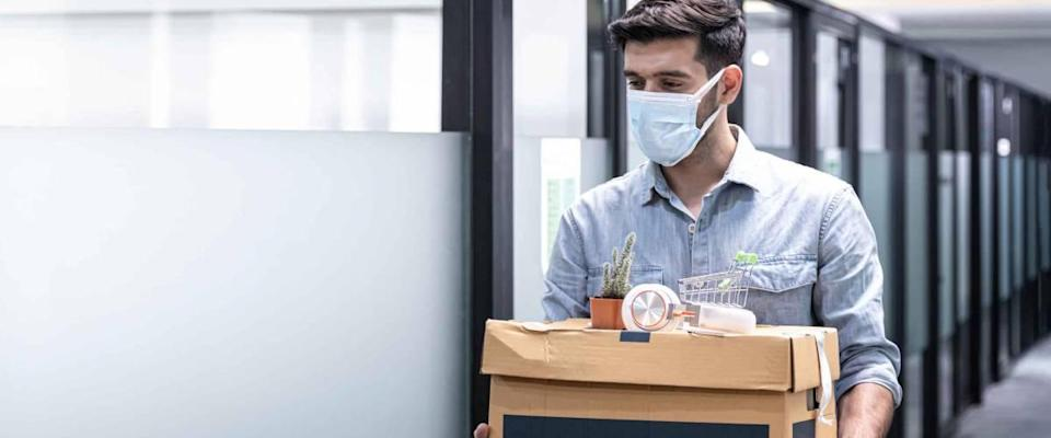Man walking out of an office holding box of things, wearing a mask