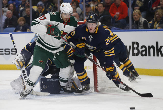 Buffalo Sabres defenseman Rasmus Dahlin, right, and Minnesota Wild forward Marcus Foligno, left, battle for the puck during the second period of an NHL hockey game, Tuesday, Feb. 5, 2019, in Buffalo N.Y. (AP Photo/Jeffrey T. Barnes)