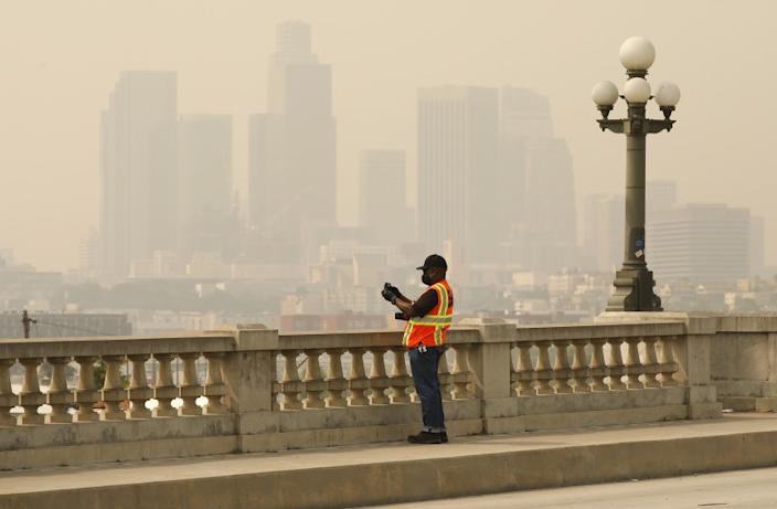 """Brooks Hubbard with the U.S. Army Corps of Engineers takes photos from the historic North Broadway Bridge over the Los Angeles River Tuesday morning as smoke and ash from the Bobcat fire cloak the area. <span class=""""copyright"""">(Al Seib/Los Angeles Times)</span>"""