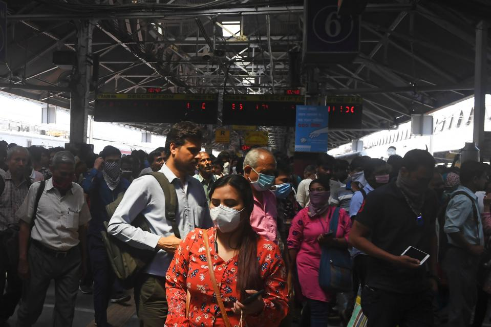 Passengers wearing facemasks amid concerns over the spread of the COVID-19 novel coronavirus, walk along with others at the Howrah railway station, in Kolkata on March 21, 2020. (Photo by Dibyangshu SARKAR / AFP) (Photo by DIBYANGSHU SARKAR/AFP via Getty Images)