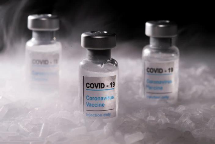 """FILE PHOTO: Vials labelled """"COVID-19 Coronavirus Vaccine"""" are placed on dry ice in this illustration"""