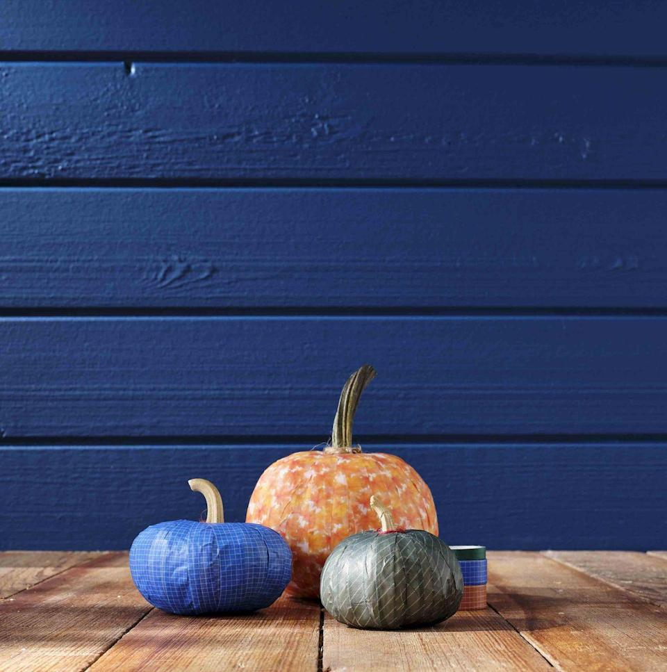 <p>Washi tape is a simple and impactful way to turn a plain-ole pumpkin into a colorful display.<strong><br></strong></p><p><strong>Make the pumpkin:</strong> Fully cover a small or medium pumpkin vertically with lengths of washi tape. Once covered, attach a piece of twine around the base of the stem, holding it in place with hot glue. </p>