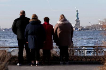 People look toward the Statue of Liberty from Battery Park following a U.S. government shutdown in Manhattan, New York, U.S., January 20, 2018. REUTERS/Andrew Kelly