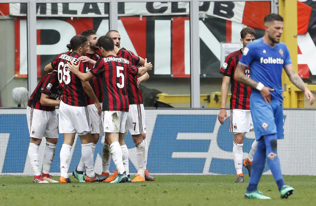 AC Milan's Patrick Cutrone, covered by his teammates, celebrates after scoring his side's second goal during the Serie A soccer match between AC Milan and Fiorentina at the San Siro stadium in Milan, Italy, Sunday, May 20, 2018. (AP Photo/Antonio Calanni)
