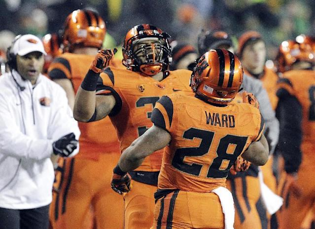 Oregon State running back Terron Ward, right, celebrates his touchdown with teammate Tyler Anderson during the first half of an NCAA college football game against Oregon in Eugene, Ore., Friday, Nov. 29, 2013. (AP Photo/Don Ryan)