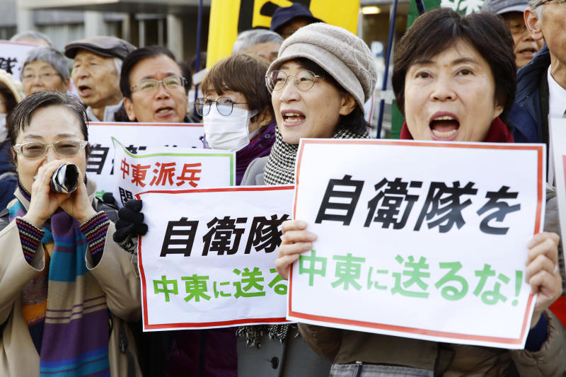 """Protesters hold placards reading """"Do not send Japan's Self-Defense Forces to Middle East"""" outside the prime minister's official residence in Tokyo Friday, Dec. 27, 2019. Japan on Friday approved a contentious plan to send its naval troops to the Middle East to contribute to the peace and stability in the area and ensure the safety of Japanese ships transporting oil, a mission crucial to an energy-poor country that heavily depends on oil imports from the region. (Hiroki Yamauchi/Kyodo News via AP)"""