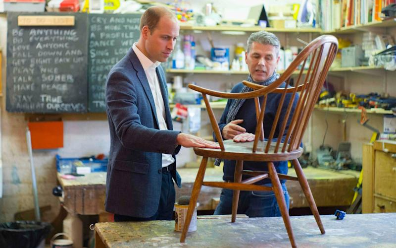 Prince William, Duke of Cambridge, talks with volunteer Bernard Bristow, during his visit to the Spitalfields Crypt Trust - AFP