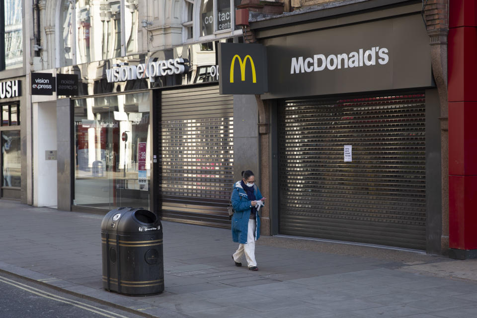 A woman in a face mask wasks past major shops on Oxford Street, closed for business. March 24th 2020 was the first day of enforced lockdown in the UK, in order to stop the spread of the Coronavirus Covid 19. On what would normally be a bustling business / week day in London, the city was deserted, with just a few people in masks out on the street, plus a few taxis and mostly empty buses. (photo by Phil Clarke Hill/In Pictures via Getty Images)