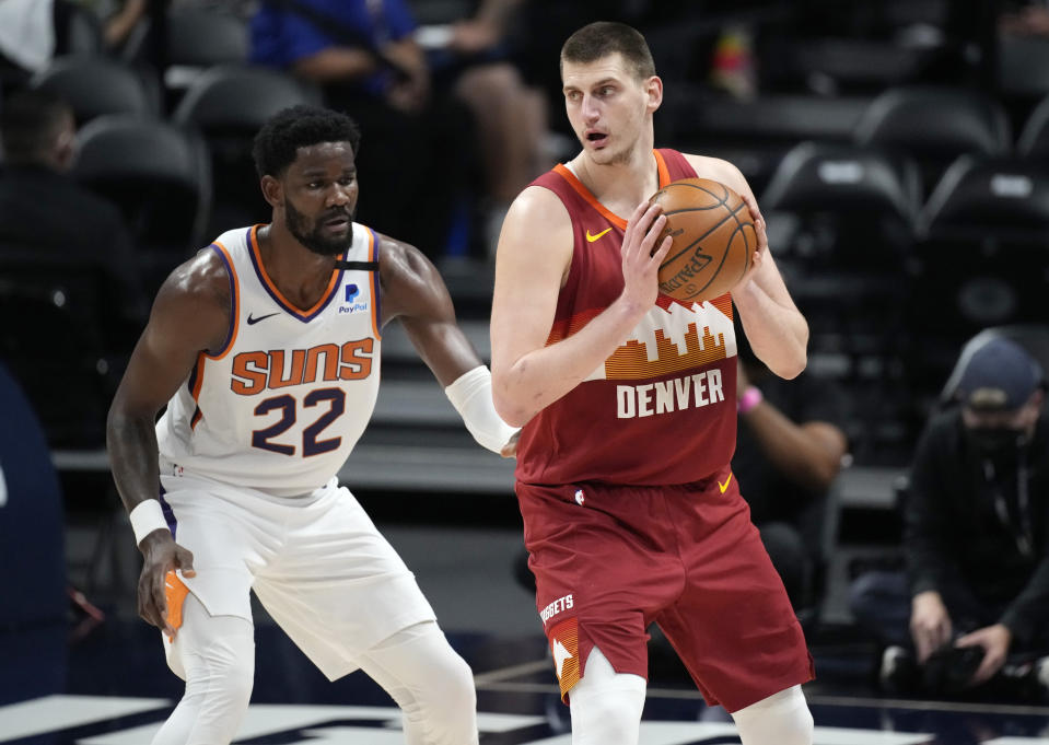 Denver Nuggets center Nikola Jokic, right, looks to pass the ball as Phoenix Suns center Deandre Ayton defends in the first half of Game 4 of an NBA second-round playoff series Sunday, June 13, 2021, in Denver. (AP Photo/David Zalubowski)