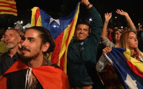 People hold Catalan flags as they listen to Catalan President Carles Puigdemont speak via a televised press conference as they await the result of the Indepenence Referendum at the Placa de Catalunya - Credit: Getty