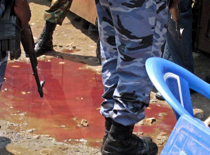 Armed security officers stand around a pool of blood at the scene of an attack by armed raiders on September 19, 2011 in the capital Bujumbura (AFP Photo/Esdras Ndikumana)