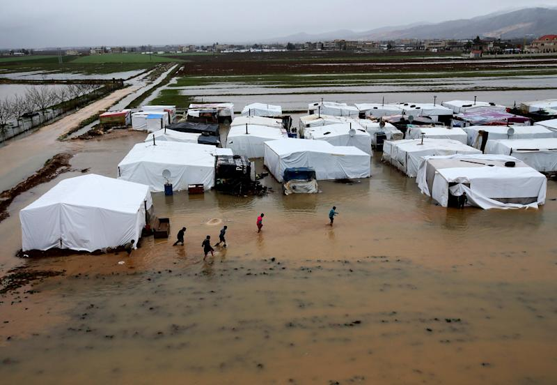 FILE - In this January 8, 2013 file photo, Syrian refugees make their way in flooded water at a temporary refugee camp, in the eastern Lebanese Town of Al-Faour near the border with Syria, Lebanon. A housing unit designed for the United Nations' refugee agency to offer shelter for those, fleeing conflict has become the latest source of friction between Lebanese politicians and aid organizations trying to manage the massive number of Syrian refugees in the country. Lebanon's refusal to set up any kind of organized accommodation for tens of thousands of Syrians, including refugee camps. (AP Photo/Hussein Malla, File)