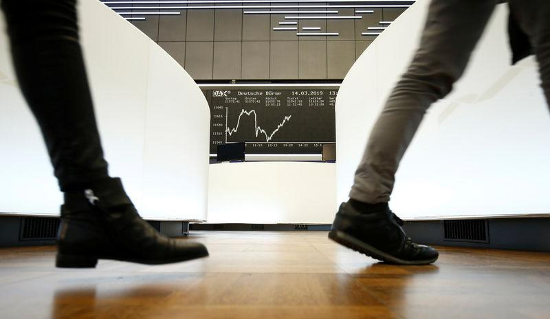 FILE PHOTO: Traders walk past the German share price index DAX graph at Frankfurt's stock exchange in Frankfurt