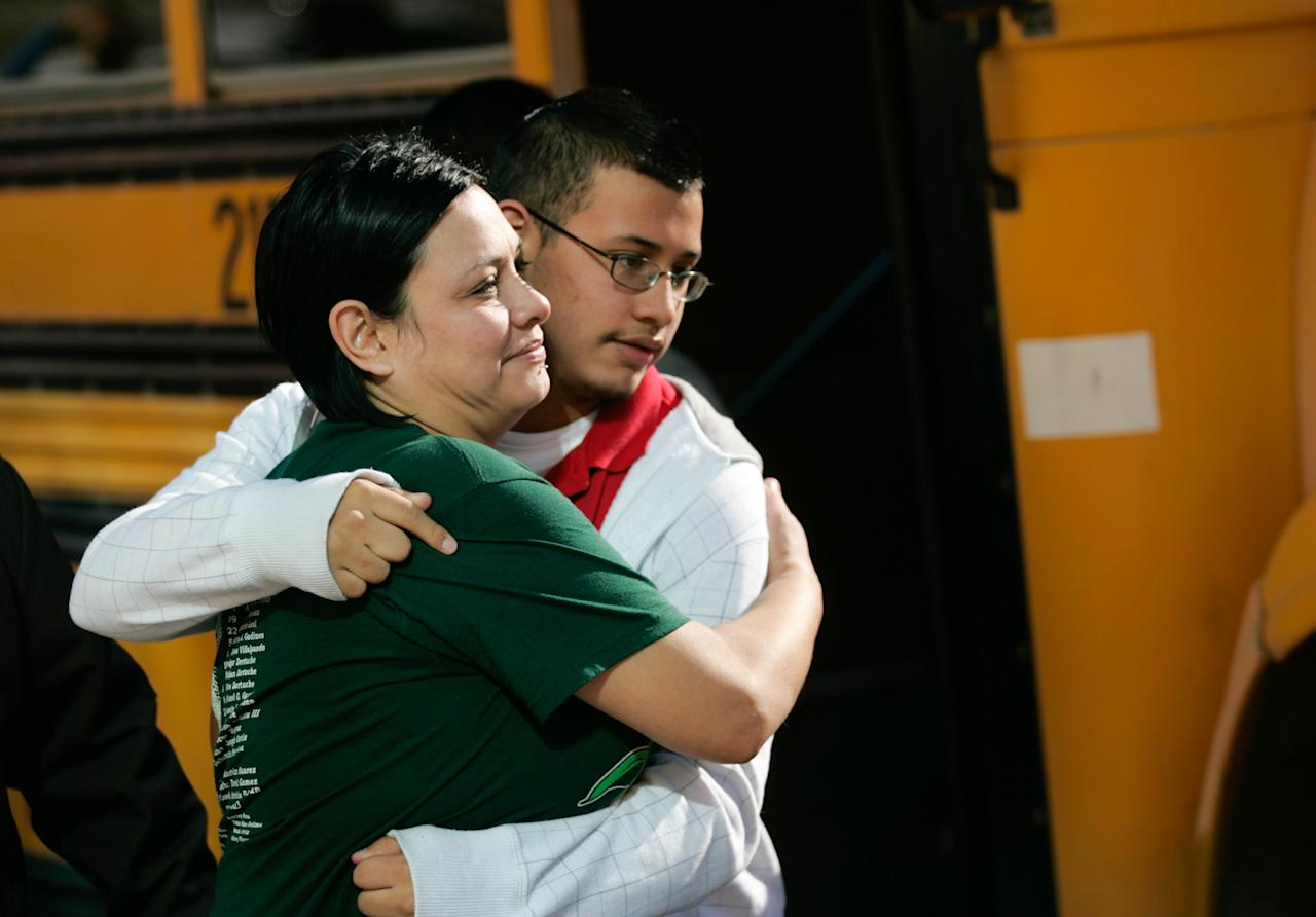 Jennifer Davila, left, tightly embraces her son Jordan as he is escorted into a park near Cummings Middle School, Wednesday, Jan. 4, 2012, in Brownsville Texas, after a fatal shooting at the school Wednesday morning. Officers summoned to a locked-down Texas middle school on Wednesday shot and killed an eighth-grader after he ignored their order to drop a handgun he was brandishing and instead pointed it at them, police said. (AP Photo/The Brownsville Herald, Yvette Vela)